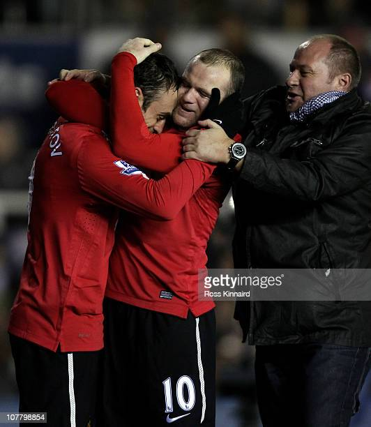 Dimitar Berbatov of Manchester United is congratulated by team mate Wayne Rooney and a pitch invader after scoring the opening goal during the...
