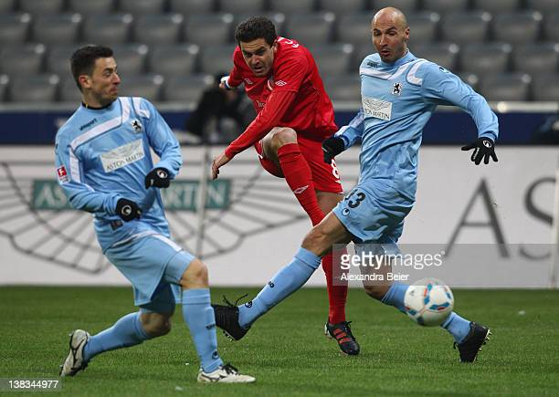 Dimitar Rangelov of Energie Cottbus shoots against Necat Ayguen and Antonio Rukavina during the German second league match between 1860 Muenchen and...