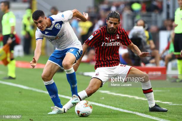 Dimitri Bisoli of Brescia Calcio competes for the ball with Ricardo Rodriguez of AC Milan during the Serie A match between AC Milan and Brescia...