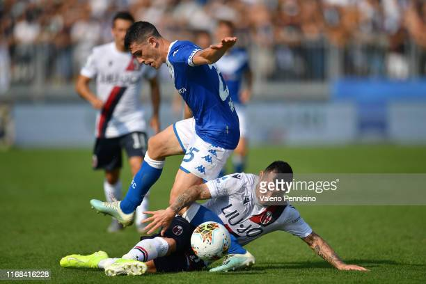 Dimitri Bisoli of Brescia Calcio is tackled by Gary Medel of Bologna FC during the Serie A match between Brescia Calcio and Bologna FC at Stadio...