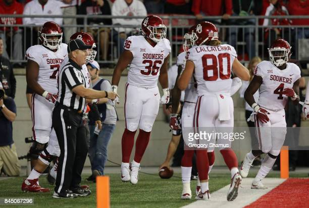 Dimitri Flowers of the Oklahoma Sooners celebrates with teammates after scoring a 36yard receiving touchdown during the third quarter against the...