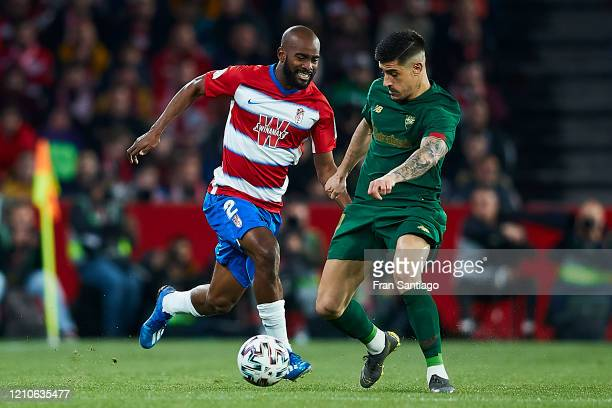 Dimitri Foulquier of Granada CF competes for the ball with Yuri Berchiche of Athletic Club during the Copa del Rey semifinal 2nd leg match between...