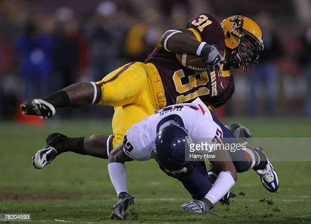 Dimitri Nance of the Arizona State takes a hit from Nate Ness of the University of Arizona Wildcats during the second quarter at Sun Devil Stadium on...