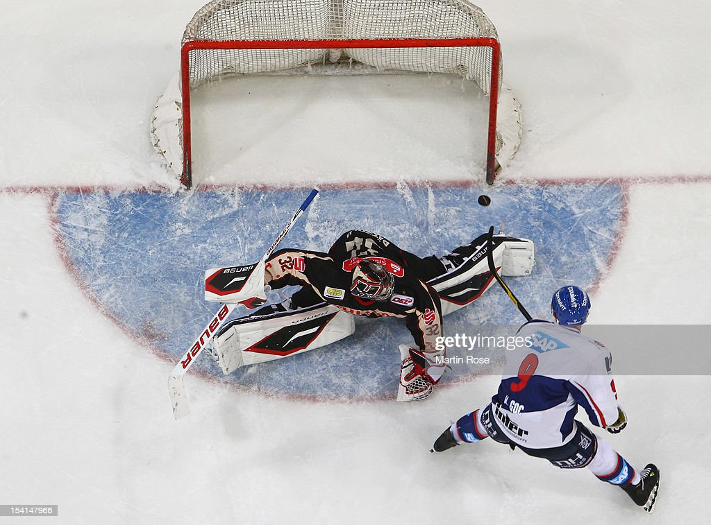 Dimitri Paetzold (L), goaltender of Hannover saves the shot of Marcel Goc (R) of Mannheim during penbalty shot out during the DEL match between Hannover Scorpions and Adler Mannheim at TUI Arena on October 14, 2012 in Hanover, Germany.