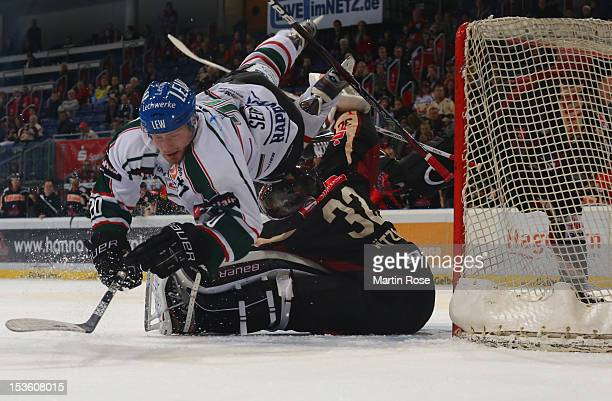 Dimitri Paetzold , goaltender of Hannover stops Patrick Seifert of Augsburg battle in front of the net during the DEL match between Hannover...