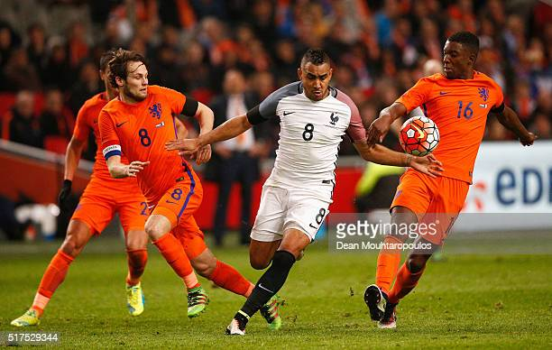 Dimitri Payet of France is challenged by Daley Blind and Riechedly Bazoer of the Netherlands during the International Friendly match between...