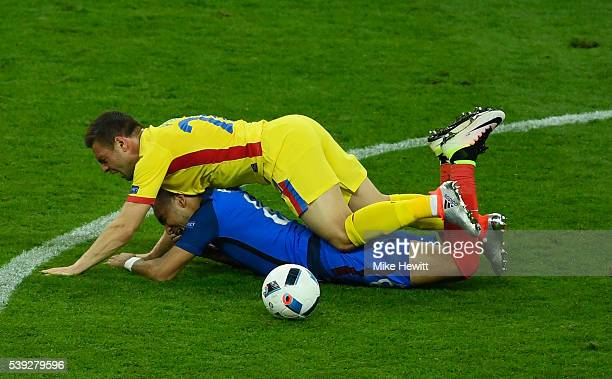 Dimitri Payet of France is chellenged by Adrian Popa of Romania during the UEFA Euro 2016 Group A match between France and Romania at Stade de France...