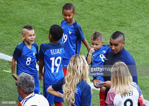 Dimitri Payet of France talks to his wife Ludivine while children play after the UEFA EURO 2016 round of 16 match between France and Republic of...