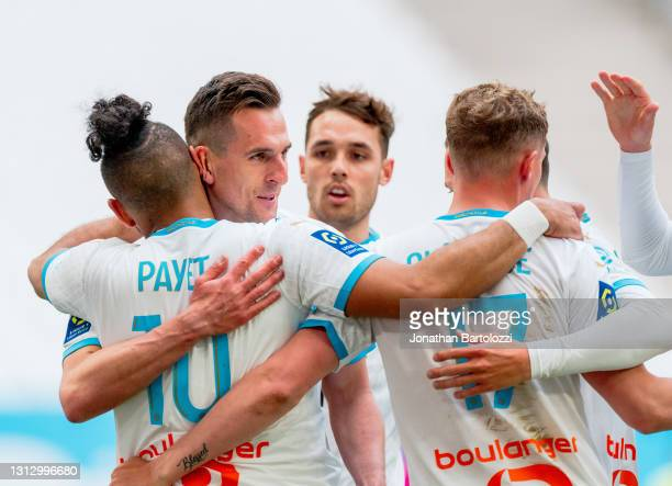 Dimitri Payet of Olympique de Marseille celebrates with teammate Arkadiusz Milik and Michaël Cuisance after scoring during the Ligue 1 match between...