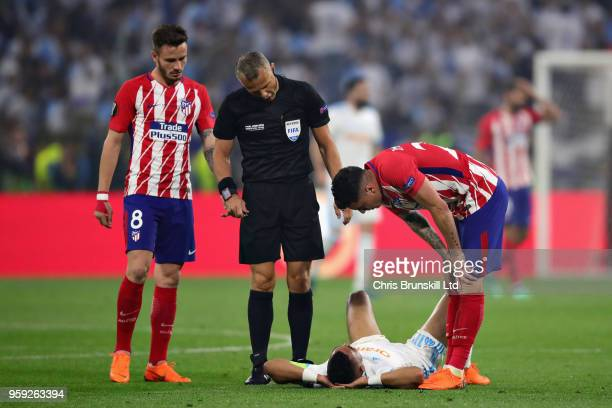 Dimitri Payet of Olympique de Marseille talks with Jose Gimenez of Club Atletico de Madrid and Referee Bjorn Kuipers after getting injured during the...