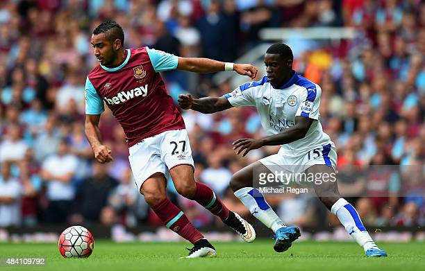 Dimitri Payet of West Ham United and Jeff Schlupp of Leicester City compete for the ball during the Barclays Premier League match between West Ham...
