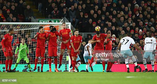 Dimitri Payet of West Ham United scores their first goal from a free kick during the Premier League match between Liverpool and West Ham United at...