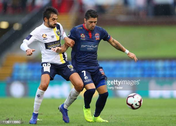Dimitri Petratos of the Newcastle Jets contests the ball with Jem Karacan of the Central Coast Marinersduring the round 22 ALeague match between the...