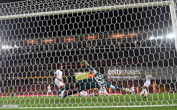 Dimitri Petratos of the Roar gets the ball past goalkeeper Simon Mignolet of Liverpool during the international friendly match between Brisbane Roar...