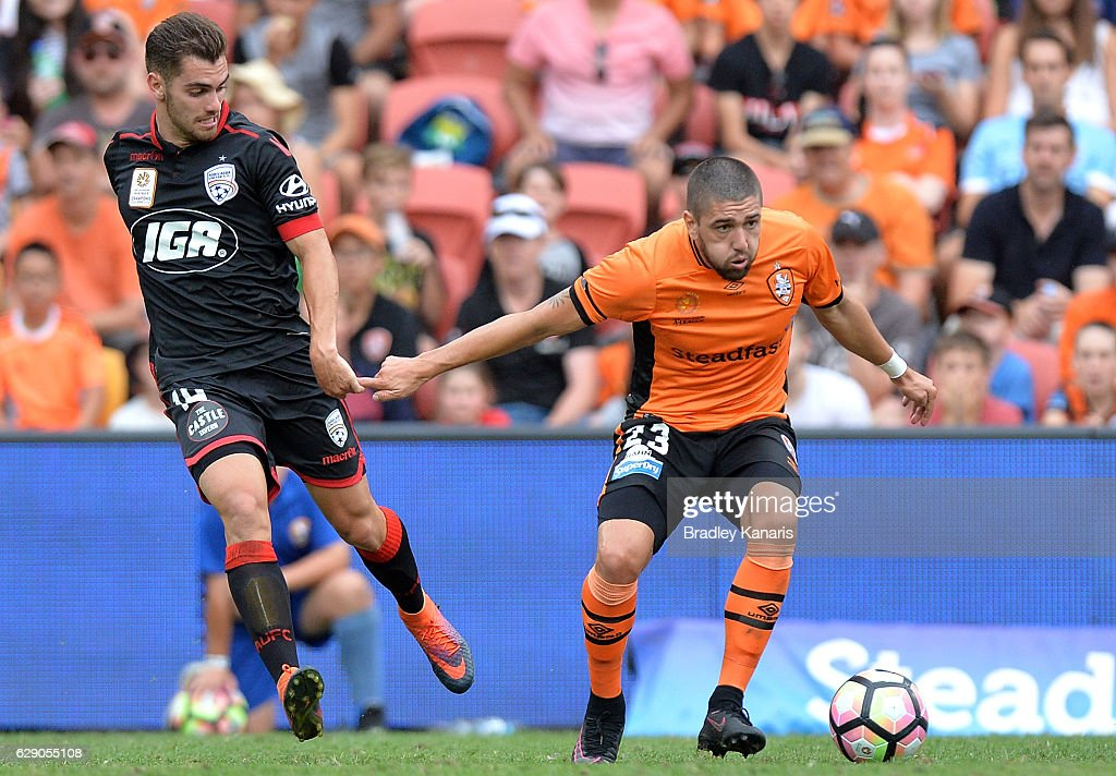 Dimitri Petratos of the Roar is challenged by Benjamin Garuccio of Adelaide during the round 10 A-League match between the Brisbane Roar and Adelaide United at Suncorp Stadium on December 11, 2016 in Brisbane, Australia.