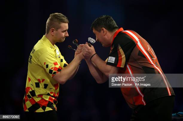 Dimitri Van den Bergh and Mensur Suljovic at the start of their match during day twelve of the William Hill World Darts Championship at Alexandra...
