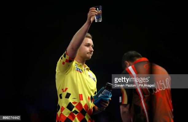 Dimitri Van den Bergh celebrates winning against Mensur Suljovic during day twelve of the William Hill World Darts Championship at Alexandra Palace...