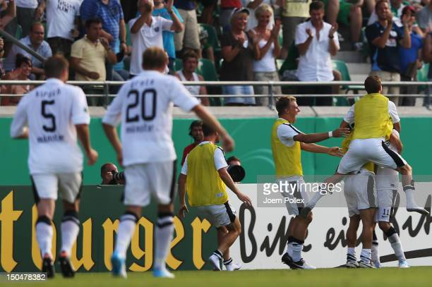 Dimitrij Nazarov of Muenster celebrates with his team mates after scoring his team's third goal during the DFB Cup first round match between Preussen...