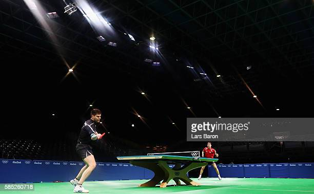 Dimitrij Ovtcharov of Germany practices with team mate Timo Boll of Germany during a training session for table tennis at the Rio Centro Pavilion for...