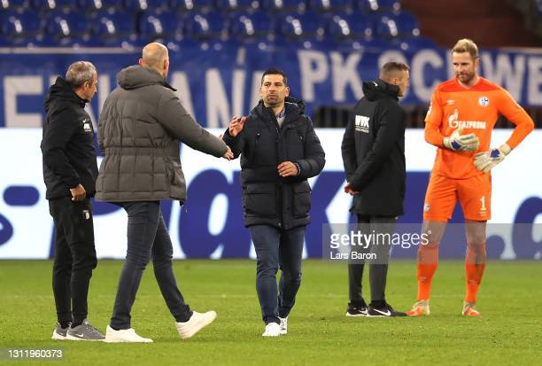 Dimitrios Grammozis, Head Coach of FC Schalke 04 interacts with Heiko Herrlich, Head Coach of FC Augsburg after during the Bundesliga match between...