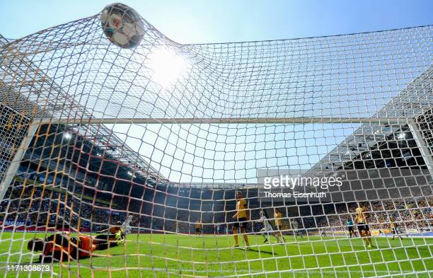 Dimitris Diamantakos of St. Pauli scores his team's first goal past goalkeeper Kevin Broll of Dresden during the Second Bundesliga match between SG...
