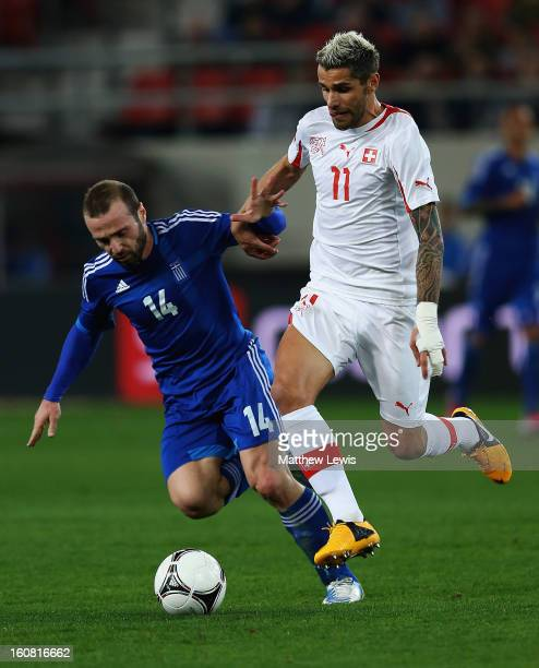 Dimitris Salpigidis of Greece and Valon Behrami of Switzerland challenge for the ball during the International Friendly match between Greece and...