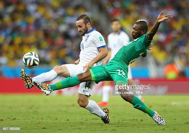 Dimitris Salpingidis of Greece and Die Serey of the Ivory Coast compete for the ball during the 2014 FIFA World Cup Brazil Group C match between...
