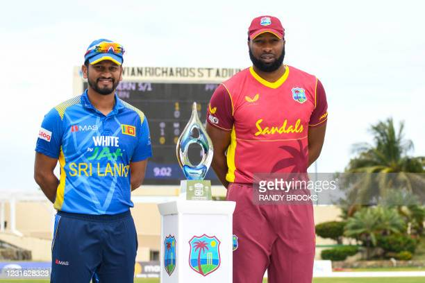 Dimuth Karunaratne of Sri Lanka and Kieron Pollard of West Indies pose with the trophy at the start of the 1st ODI match between West Indies and Sri...