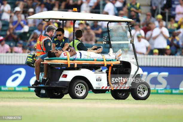 Dimuth Karunaratne of Sri Lanka is stretchered off the field after being struck by a delivery from Pat Cummins of Australia during day two of the...