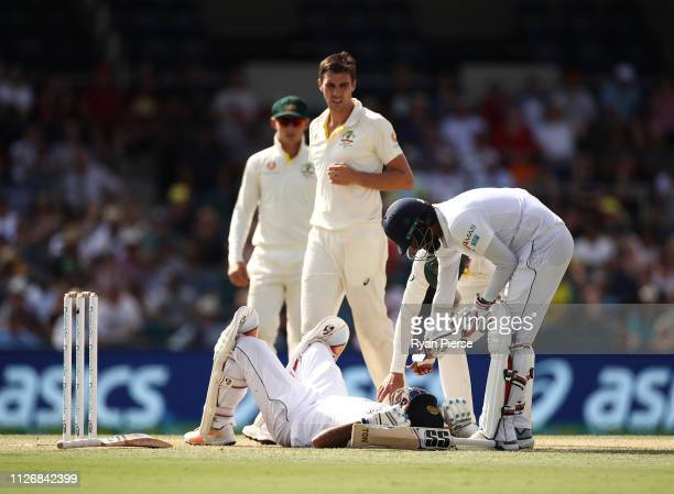 Dimuth Karunaratne of Sri Lanka is struck by a delivery frok Pat Cummins of Australia during day two of the Second Test match between Australia and...