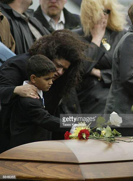 Dina Amos stepmother of US Army Pfc John Amos II helps eightyearold Hunter Amos brother of John Amos II place a flower on the casket of John Amos II...