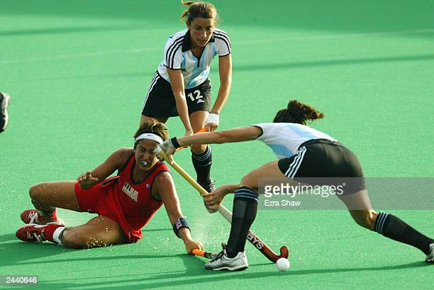 Dina Rizzo of the United States goes sliding for the ball while defended by Mariana Gonzalez and Marina DiGiacomo of Argentina at Parque Del Este on...