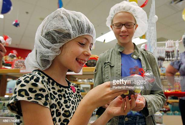 Dinah Routhier joined by sister Sophie right smiles when she gets a sample bag of candy Wednesday Aug 12 2015 following a tour at Haven's Candies...