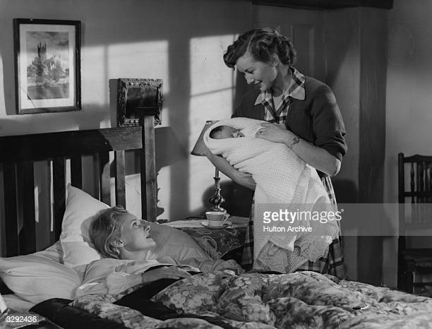 Dinah Sheridan holds the baby for mother Ann Todd the blonde British actress who was married to director David Lean She is lying in bed just after...