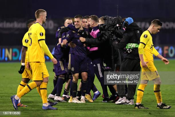 Dinamo Zagreb players and staff celebrate victory as Eric Dier and Giovani Lo Celso of Tottenham Hotspur look dejected following the UEFA Europa...