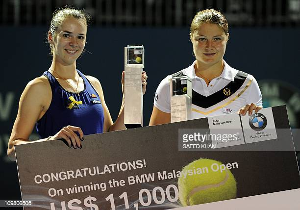 Dinara Safina of Russia and her partner Galina Voskoboeva of Kazakistan pose for pictures with the winning trophies during a prize distribution...