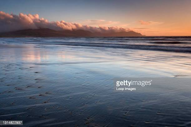 Dinas Dinlle beach backed by the mountains of the Lleyn Peninsula at sunset.
