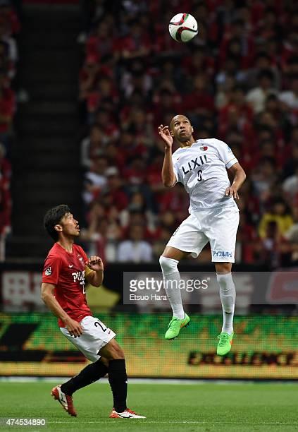 Dinei of Kashima Antlers outjumps Yuki Abe of Urawa Reds during the JLeague match between Urawa Red Diamonds and Kashima Antleres at Saitama Stadium...