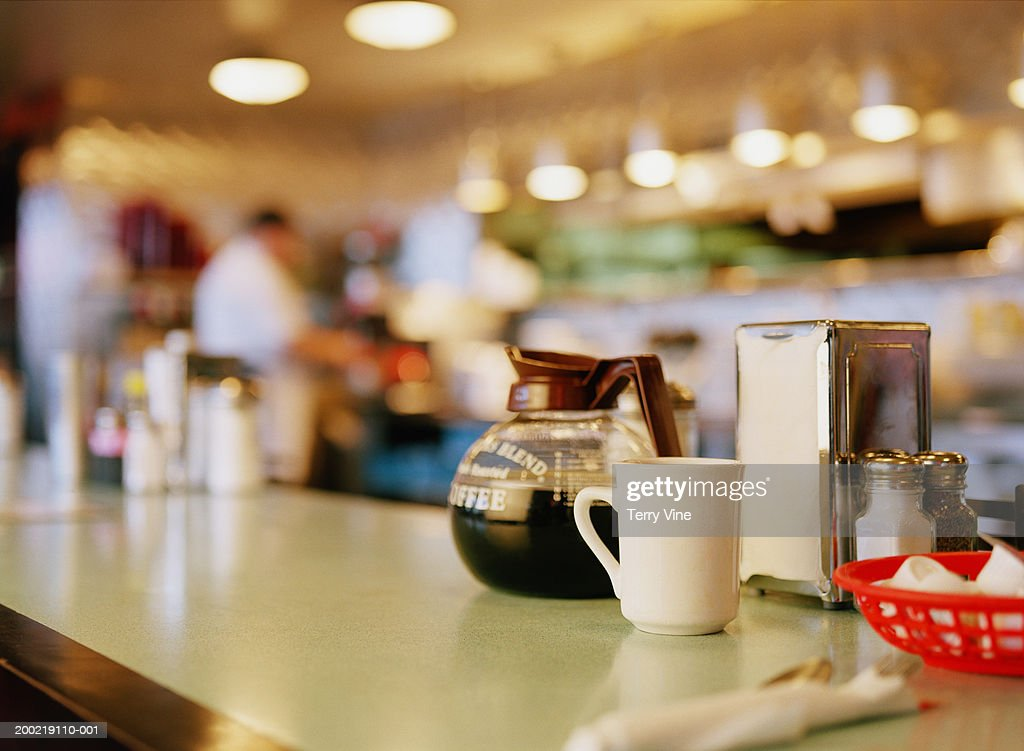 Diner counter top with coffee pot and cup next to napkin dispenser : Stock Photo