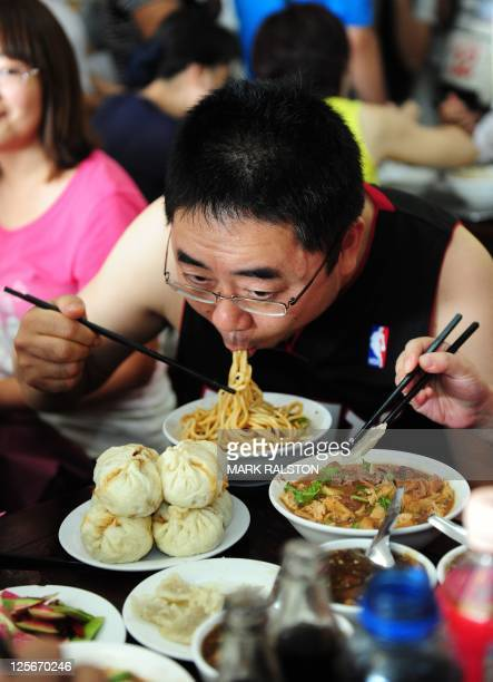 A diner enjoys a bowl of 'Pork Noodles in Brown Bean Sauce' in the crowded the Yaoji Chaogan restaurant after the restaurant's popularity soared due...