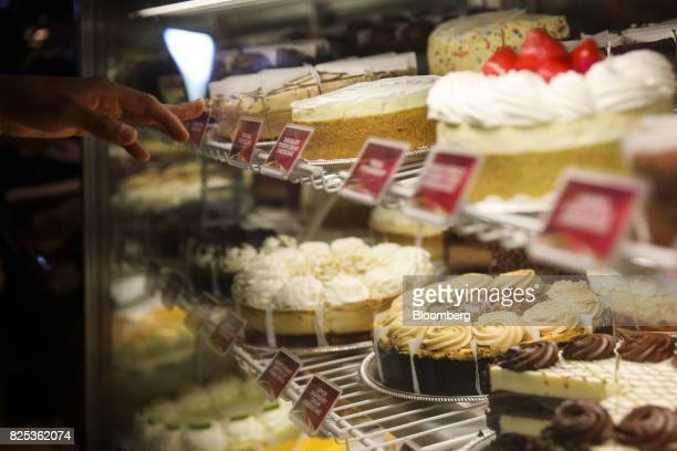 A diner points to a display case of flavored cheesecakes at a Cheesecake Factory Inc restaurant in the Canoga Park neighborhood of Los Angeles...