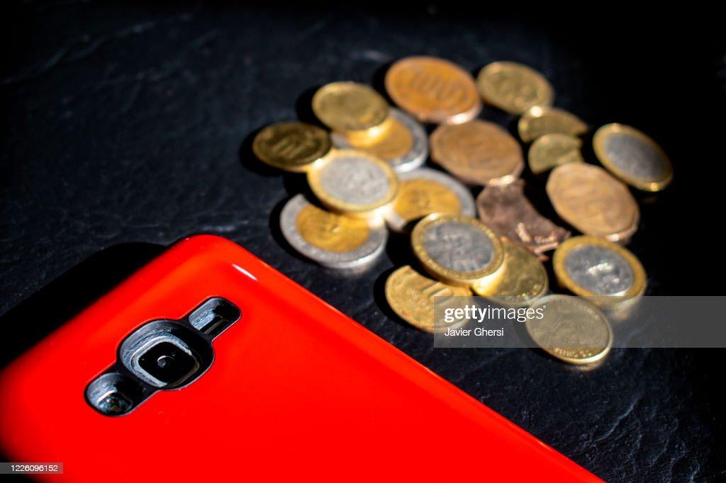 Dinero en efectivo: pesos chilenos en monedas y teléfono celular/móvil con protector rojo : Stock Photo