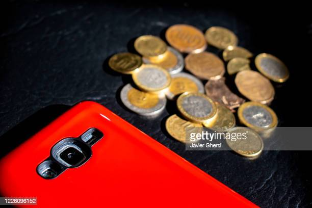 dinero en efectivo: pesos chilenos en monedas y teléfono celular/móvil con protector rojo - teléfono móvil stock pictures, royalty-free photos & images