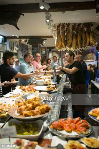 Diners and staff in pintxos tapas snack bar restaurant in San Sebastian Donostia in Basque Country Spain