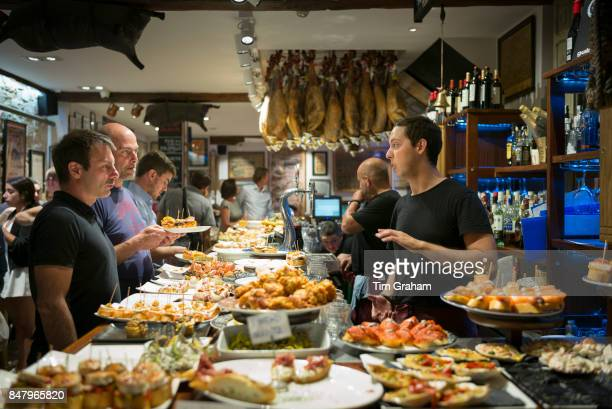 Diners and staff in pintxos tapas snack bar restaurant in San Sebastian, Donostia, in Basque Country, Spain.