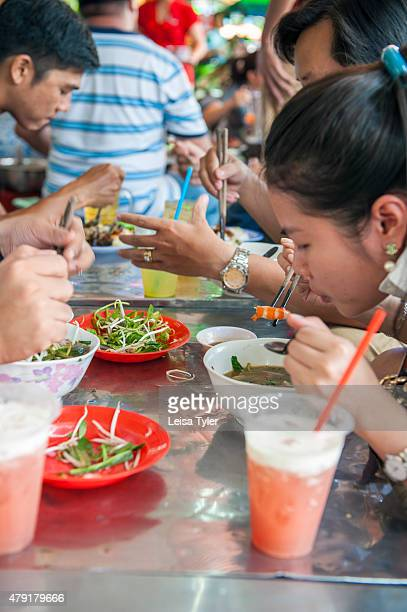 Diners at sidewalk diner Bun Mam Dac San eating Bun Mam a pungent fermented fish soup and a southern Vietnamese delicacy in Saigon