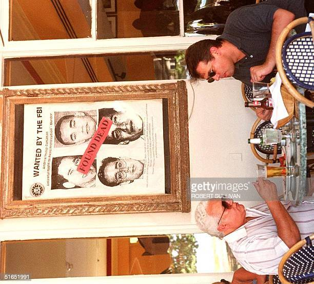 Diners at the Breakwater Hotel on Miami Beach, FL, sit 24 July under a large FBI poster of Gianni Versace murder suspect Andrew Cunanan. Miami Beach...