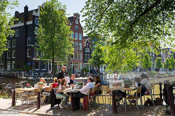Diners dining al fresco at pavement canalside cafe by Brouwersgracht and Herengracht canal, Jordaan District, Amsterdam, Netherlands. , Holland