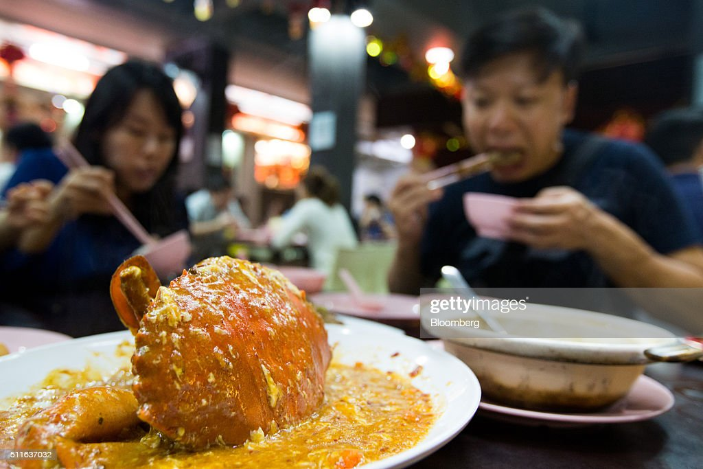 Diners eat a dish of chili crab at restaurant in Singapore, on Friday, Feb. 19, 2016. Singapore's Finance Minister Heng Swee Keat said Asia's structural growth story remains intact despite an increase in financial market turbulence that's hit countries from China to Indonesia. Photographer: SeongJoon Cho/Bloomberg via Getty Images