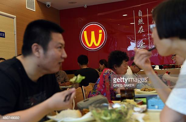 Diners eat at Wei Jia Liang Pi a small chain of popular restaurants in Beijing on June 17 2014 The fast food eatery which features a golden 'W' logo...